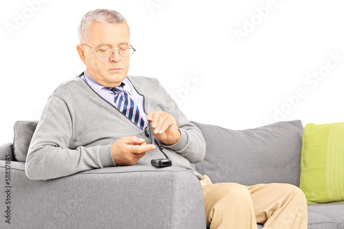Mature seated on a sofa measuring sugar level in blood
