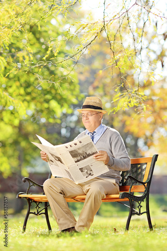 Senior gentleman with hat sitting on bench and reading a newspap