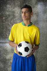 Young Brazilian Soccer Player in Uniform Holds Football