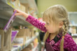 Adorable girl select chocolate bars on shelf in supermarket
