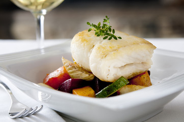 pan-seared halibut on a bed of roasted vegetables.