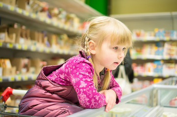 Adorable girl select products at fridge in supermarket