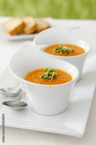 Closeup of two small bowls of carrot soup.