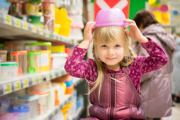 Adorable girl play with plastic containers on head in supermarke