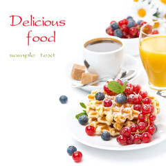 delicious breakfast with waffles, berries, orange juice