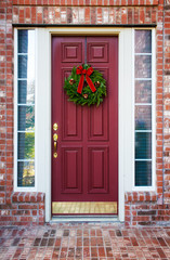 Christmas wreath hanging on a red door