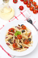 pasta with sausage, cherry tomatoes and olives, top view