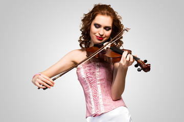 young attractive woman in pink corset on a violin