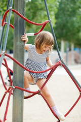 girl in dress climbing on ropes