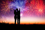 young couple standing on the hill and watching the fireworks
