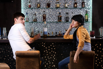Young man and woman chatting at the bar