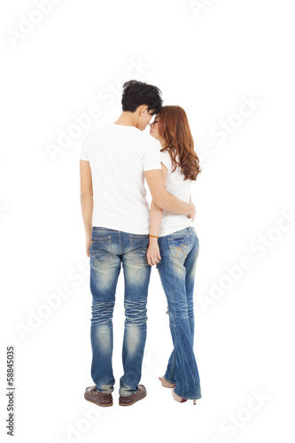 rear view of young couple looking and kissing