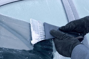 winter driving - scraping ice from a car window