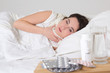 young sick woman lying and pills on the bedside table