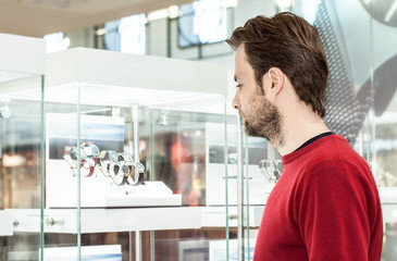 Man looking at shop window or display case in shopping center