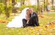 Happy newly married couple sitting on grass at autumn park