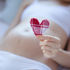 Pregnant woman holding heart. Child love concept