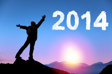 happy new year 2014.happy young man standing on the top of mount