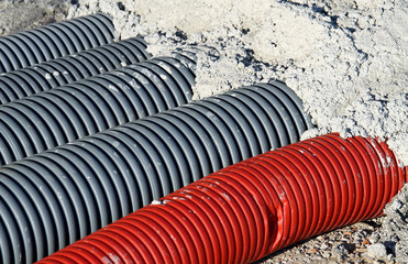 Red pvc corrugated hose and four gray pipes for laying electric