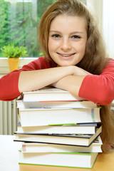 Schülerin stützt sich auf Bücher-Stapel