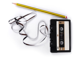 retro cassette with loose tape over a white background