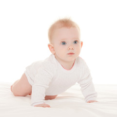 Cute baby with beautiful blue eyes on the white bed