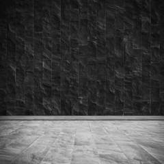 Empty dark room with slate-tiled wall and floor