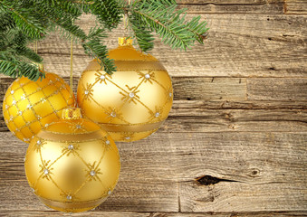 Three Gold Christmas Balls Hanging on Wooden Background