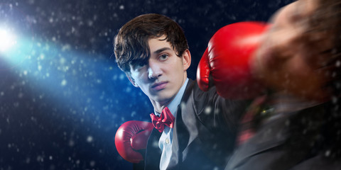 Two young businessman boxing