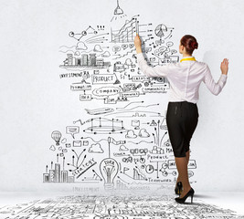 Businesswoman drawing on wall