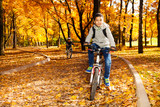 Boys riding bike in autumn park