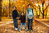 Three kids walk in autumn park
