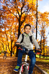 Kids on a bike in autumn park