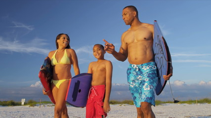 Ethnic Family Walking Ocean Carrying Surf Boards