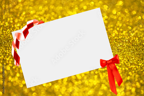 Christmas sheet of paper with bow on yellow defocused background