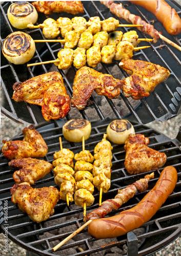 Grill mit Hühnchenflügel, Hühnchenspieß, Bratwurst, Zwiebel und