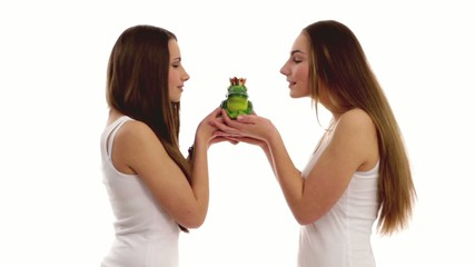 two girls kissing a frog
