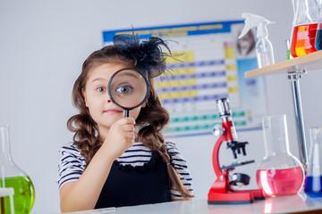 Cute dark-haired girl looking through magnifier