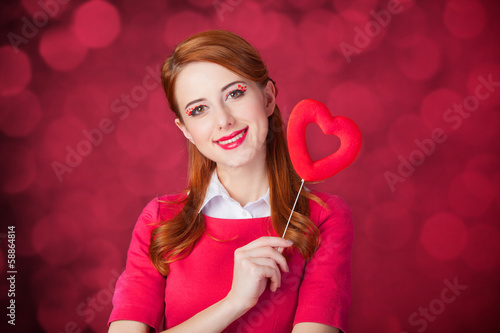 Redhead girl with shape heart toy.
