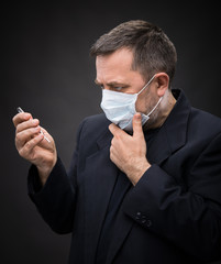 Man in medical mask with a thermometer