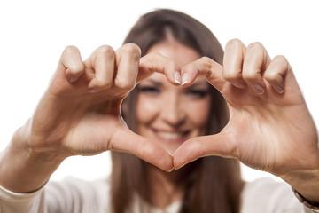 girl smiles through the fingers heart shape