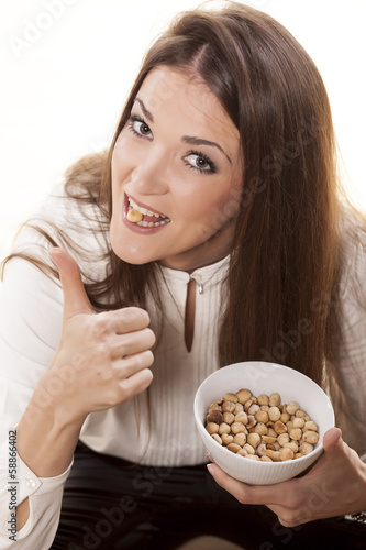 girl eating hazelnuts and shows thumb up