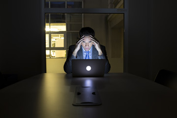 Businessman working late in his office on laptop, night light