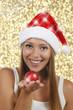 Glückliche Frau mit Nikolausmütze und roter Kugel