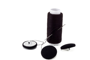 black thread with needle and buttons