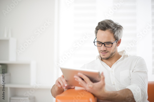 Leinwanddruck Bild handsome man surfing on tablet