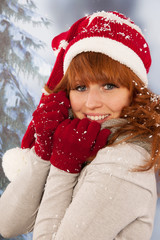 Winter woman with hat of Santa Claus in snow