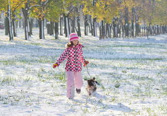 Girl running with miniature schnauzer on snow