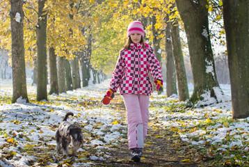 Girl walking miniature schnauzer in forest in late November
