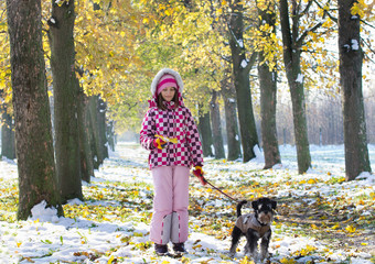 Girl walking miniature schnauzer in forest in late November